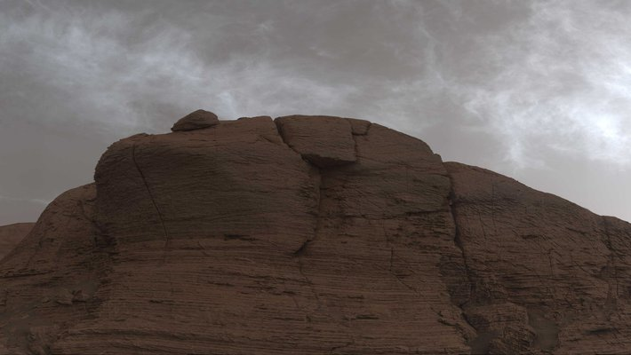 Picture of a Martian ridge with gray clouds behind it.
