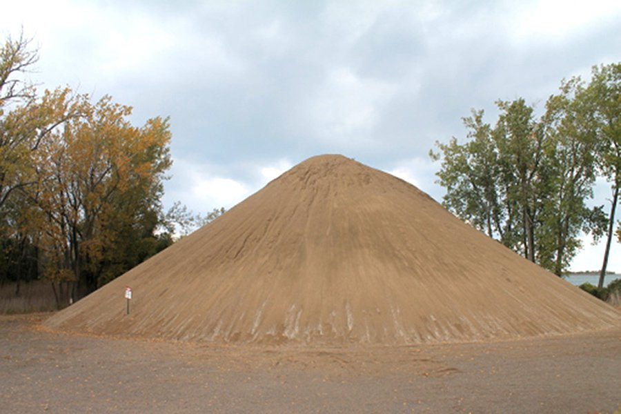 A large pile of sand sits in a vacant lot with trees behind it.