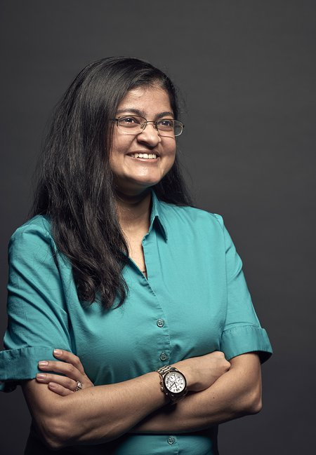 Mansi Kasliwal smiles with her arms crossed. She wears a button-down shirt in front of a black backdrop.