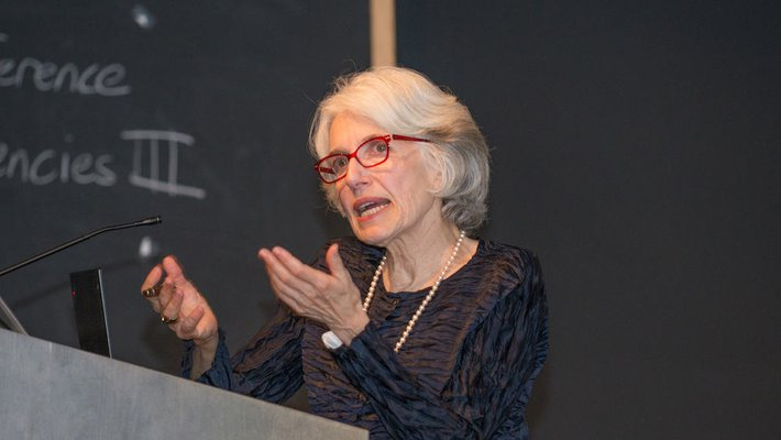 An image of Dava Sobel speaking behind a podium.