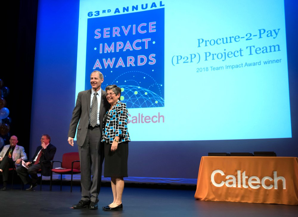 Tina Lowenthal (right), director of procurement for Purchasing Services, accepts the 2018 Team Impact Award on behalf of the P2P team.