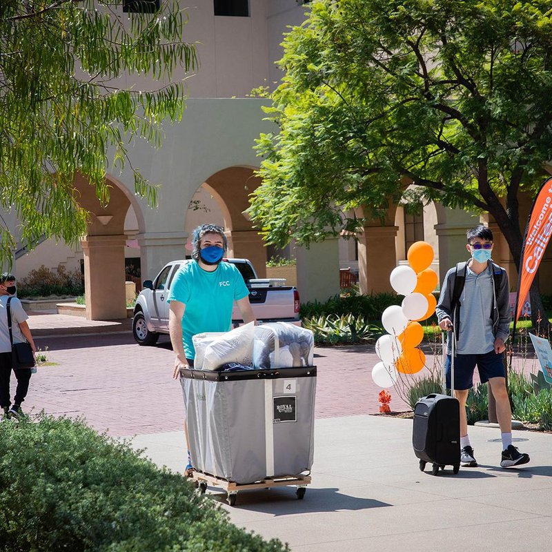 A student pushes a cart full of her belongings through campus.