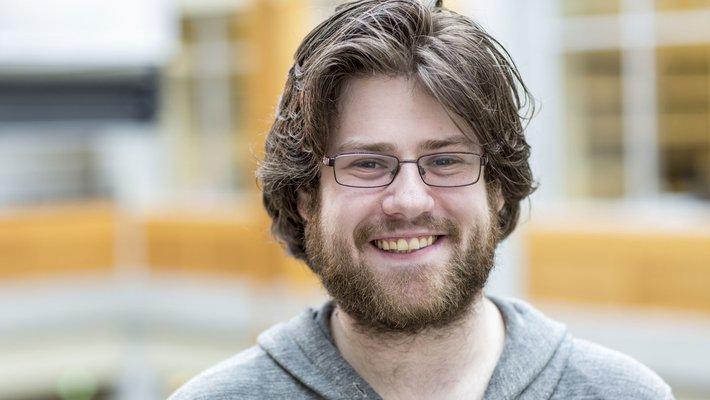 Portrait of Caltech professor Adam Blank wearing glasses and a gray hooded sweartshirt