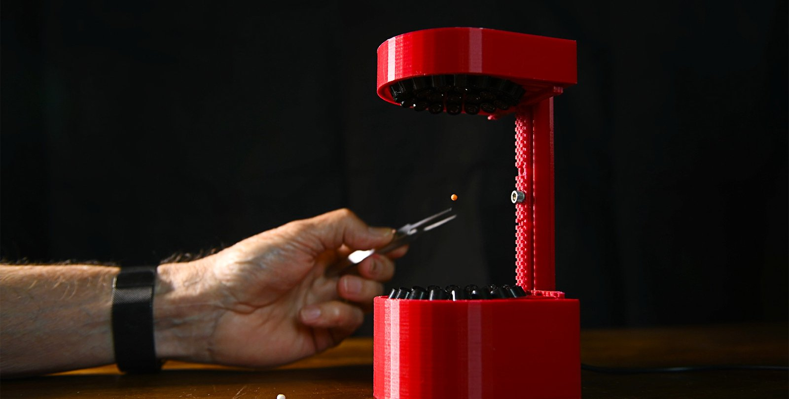 A hand places a pellet into a 3D-printed ultrasonic levitator.