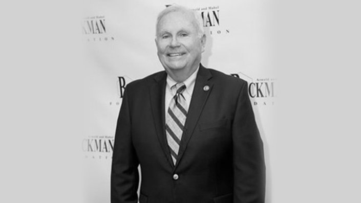 A black-and-white photo of Bill May wearing a suit and smiling.