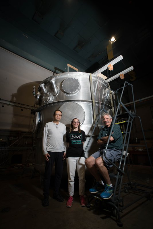 Members of the nEDM team stand in front of their magnetic cryovessel experimental apparatus