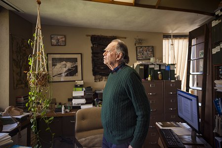 Ted Scudder, professor emeritus of anthropology, stands in his office. He is surrounded by file folders, books, and artifacts.