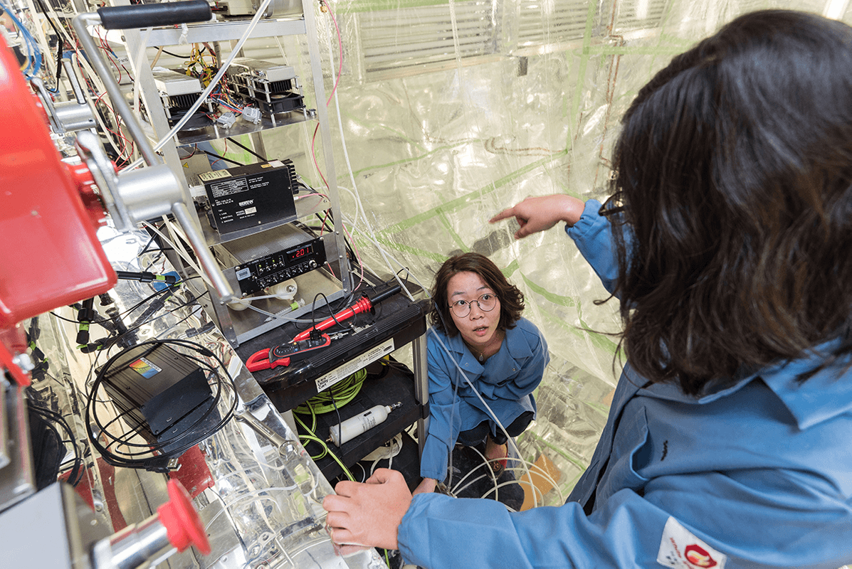 Graduate student Stephanie Kong wearing a blue lab coat looks up at a colleague while adjusting equipment inside a room that holds an atmospheric chamber. She is surrounded by wires, equipment, and the floor to ceiling plastic of the chamber walls