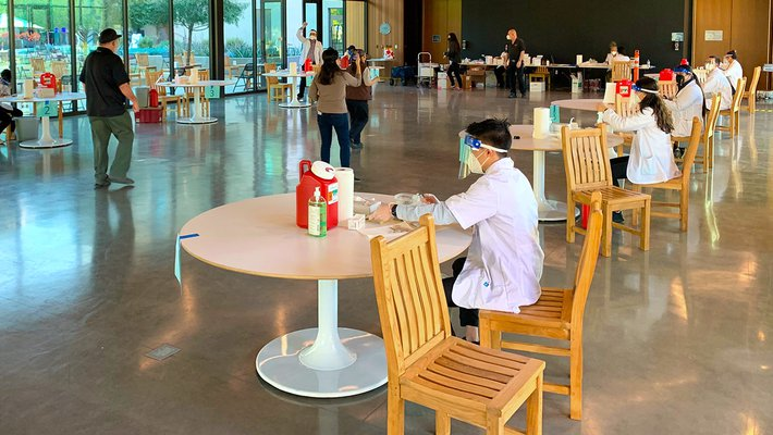 White-coated workers sit at widely spaced tables with vaccines shots at the ready.