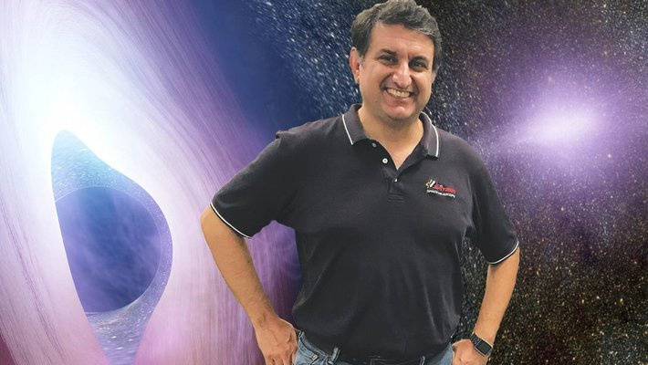 Varoujan Gorjian standing in front of an artist's rendering of the gaseous accretion disk of an active galactic nucleus