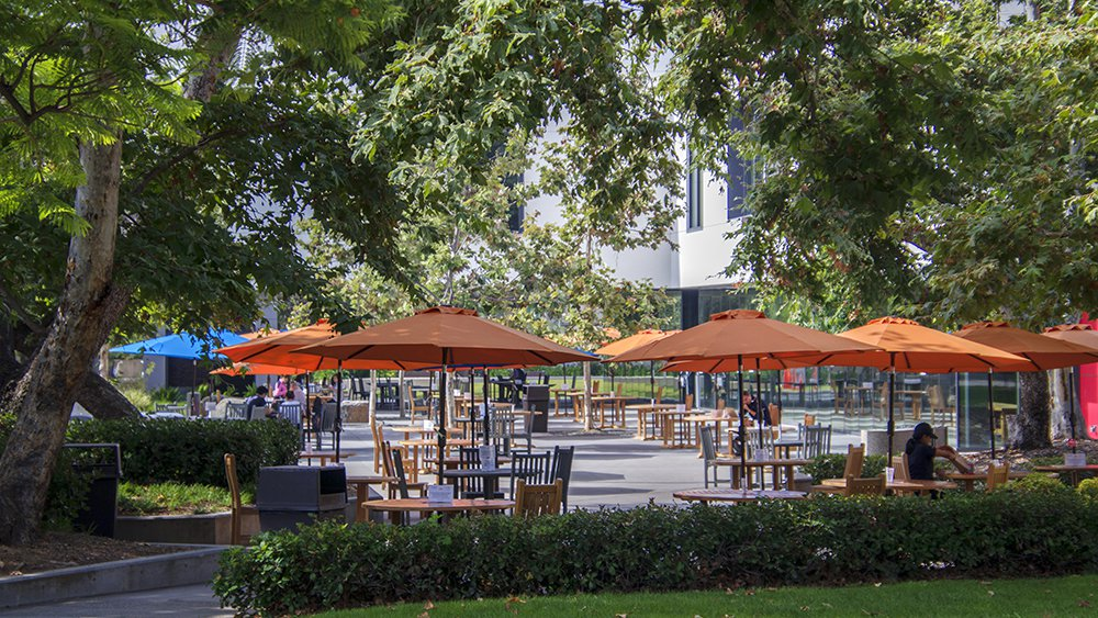 Photo of Caltech's campus featuring outdoor picnic tables covered by orange umbrellas