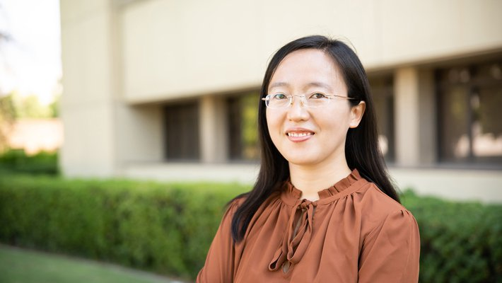 A portrait of Shasha Chong. She smiles at the camera and stands in front of a campus building with trees and grass in the background.