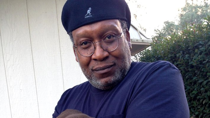 Don Crewell, former director of financial aid, holds a chocolate lab puppy and looks into the camera. He wears a beret.