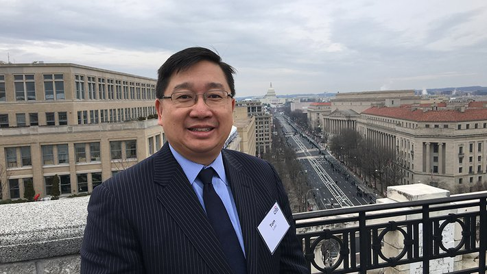 Photo of Caltech Alumnus Thomas Luke with Washington, D.C. in the background.