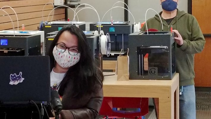 A female in the foreground and male in the background, both at 3D printers and wearing masks