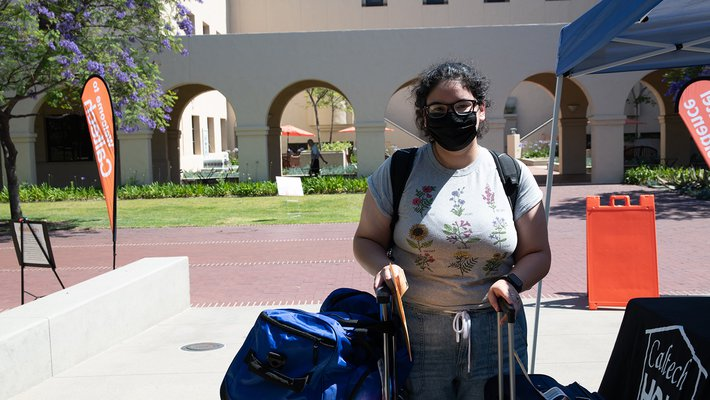 Student Jennifer Rodriguez stands with her luggage in front of the Moore Laboratory of Engineering