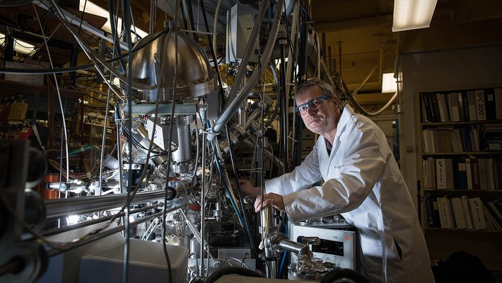 Konstantinos Giapis stands in front of his oxygen reactor. It appears as a complex tangle of tubes and wires.