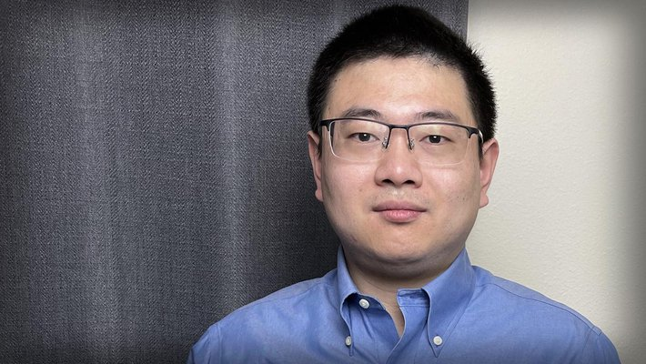 A portrait of Lei Li, who stands in his office wearing a button-down shirt and glasses.