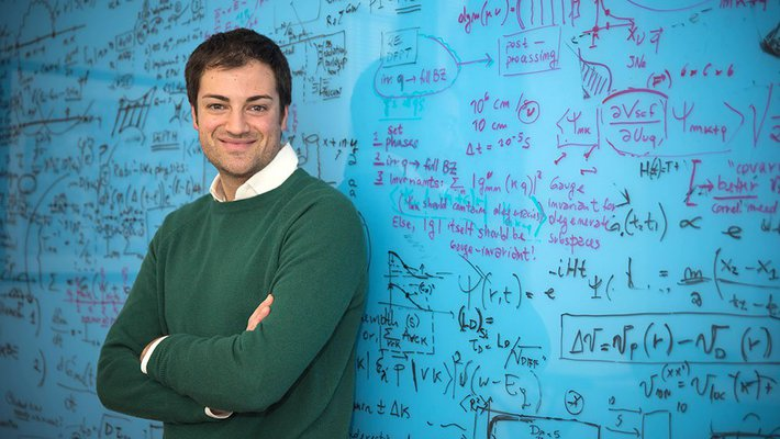 A portrait of Marco Bernardi. He stands in front of a blue chalkboard covered in writing with his arms crossed.