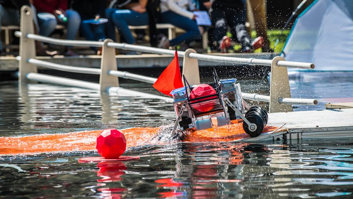 A robot splashes through Millikan Pond with a brightly-colored ball it has captured.