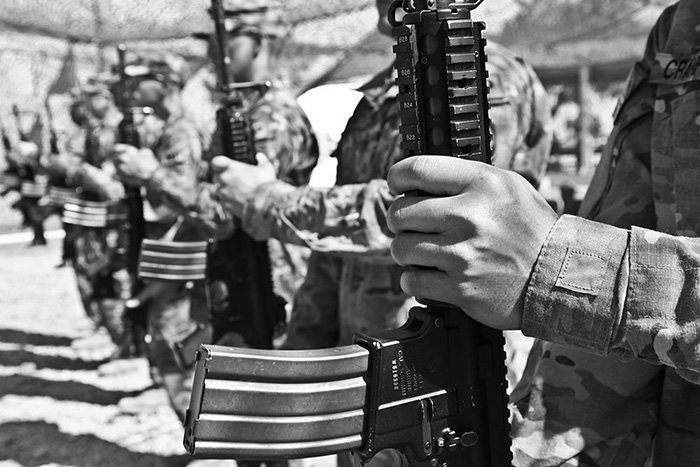 A black-and-white photo of soldiers standing in a row, holding their weapons