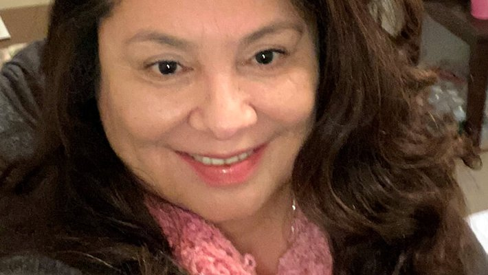 Selfie of woman smiling in her office wearing a pink scarf