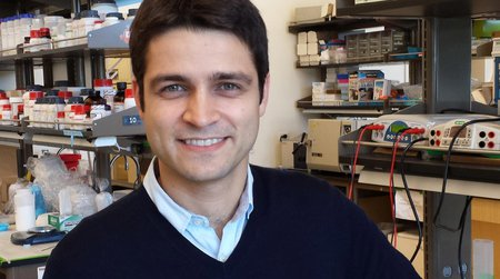 A portrait of Mikhail Shapiro in a laboratory. He wears a sweater and collared shirt. Equipment is seen in the background.