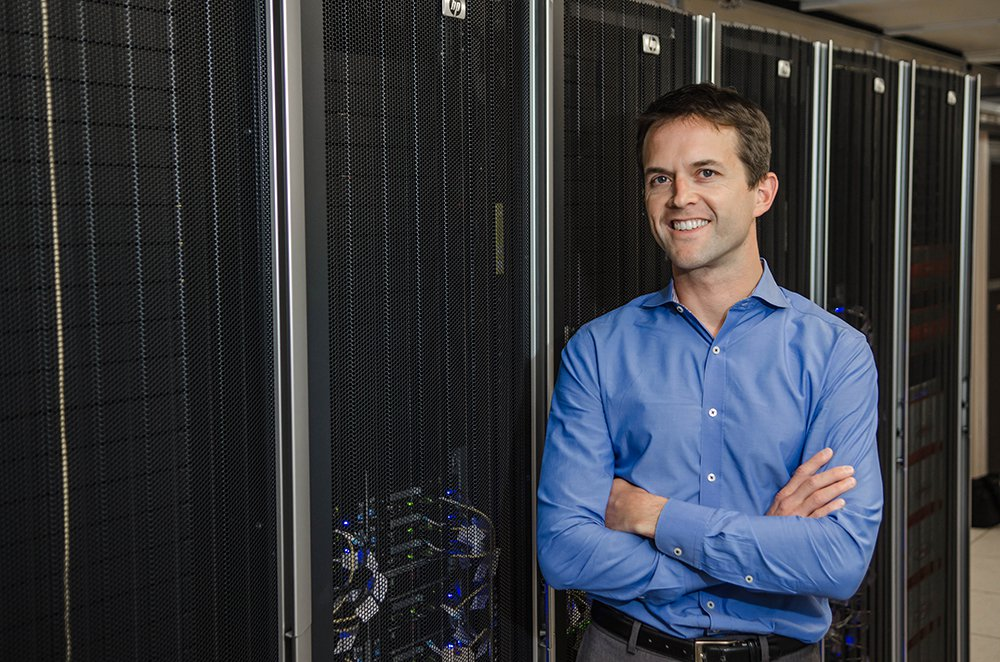 Tom Miller, professor of chemistry, stands in front of a rack of computers.