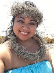 A headshot of Nikki Chun with a beach scene in the background.