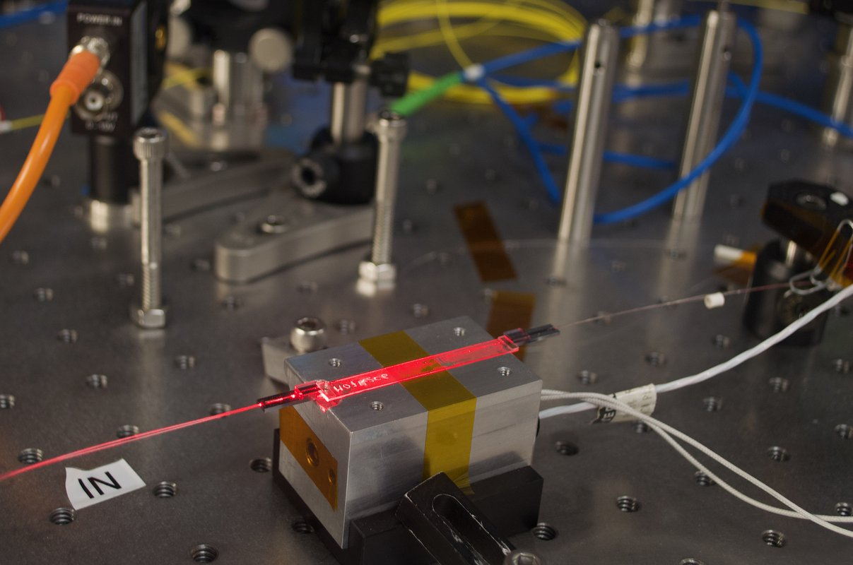 A red laser light shines through a flat waveguide on a metal workbench.