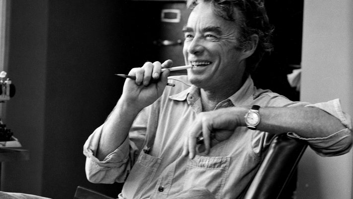 In this black-and-white photo, James Quirk sits casually in a chair, laughing and biting a pencil. He appears to be mid conversation