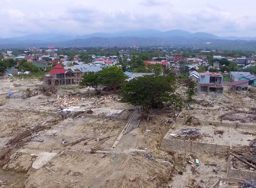 Destruction from a tsunami, leveling buildings.