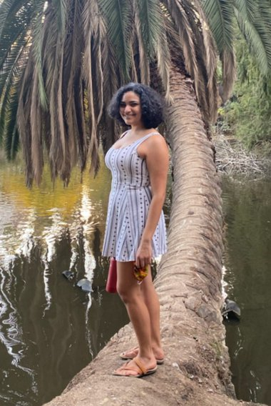 Woman posing with palm tree in background
