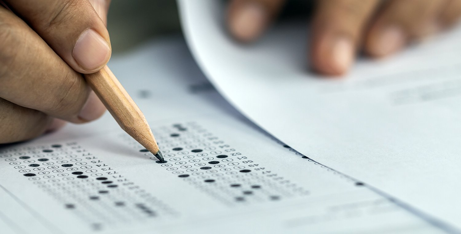 Hand with pencil fills in scantron bubbles