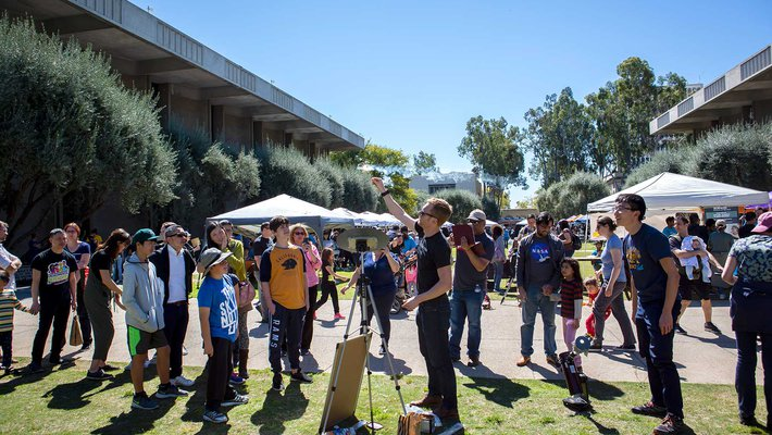 Postdoctoral scholar Cameron Hummels leads an astronomy demonstration while visitors to the second annual Science for March event watch.