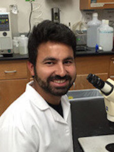 A portrait of Shashank Gandhi. He wears a lab coat and smiles while sitting in front of a microscope.
