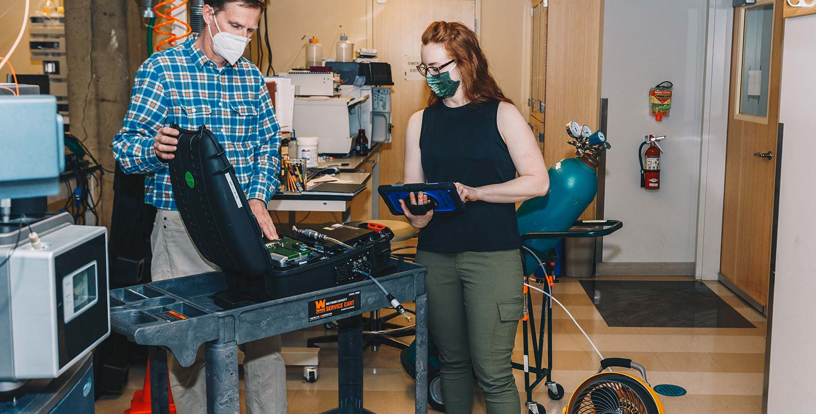 """Nathan has the GasScouter (methane detector) case open and is pointing at the battery pack. Elizabeth is holding the tablet that provides the readout from the GasScouter. The methane tank and yellow fan right behind Elizabeth are part of the gear, and in the """"ready-to-use"""" position."""