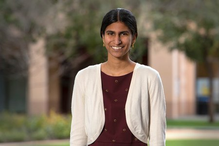 A portrait of Kavya Sreedhar. She wears a maroon blouse and white cardigan sweater