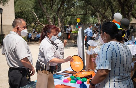 Staff members select items from a gift booth at an event celebrating employees who have been working on campus throughout the pandemic.