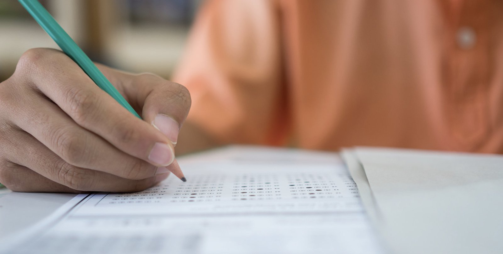 A hand holding pencil fills out a standardized test