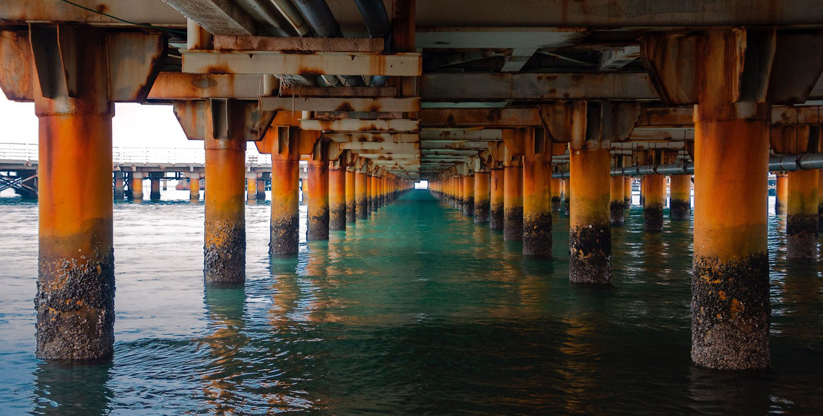 An image of the underside of a rusty bridge over a body of water.