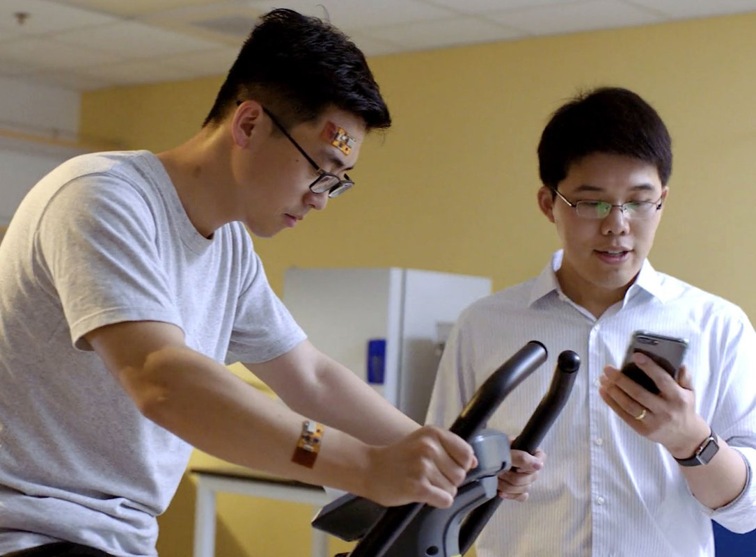 A man monitors data from flexible sweat sensors worn by a man exercising on a treadmill.