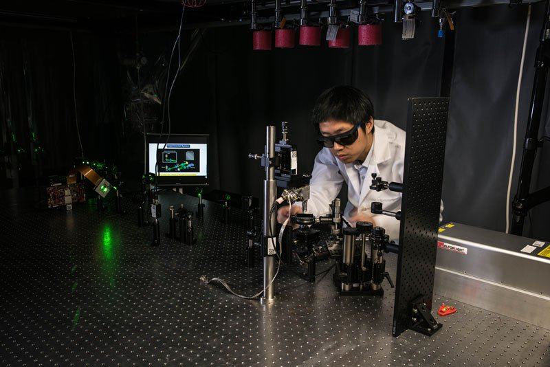 Jiamiao Yang, a postdoctoral scholar in the Caltech Optical Imaging Laboratory, adjusts a photoacoustic microscope.