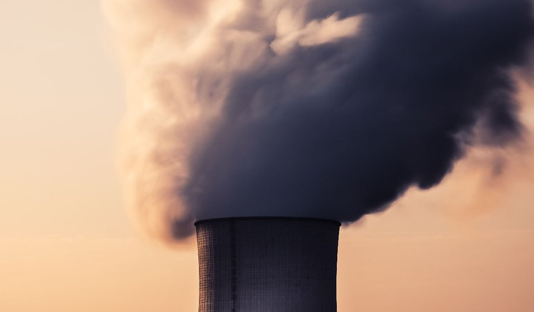 Steam billows out of a cooling tower of a power plant