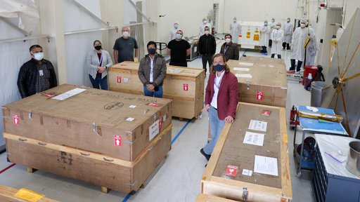 Researchers stand with crates containing spacecraft