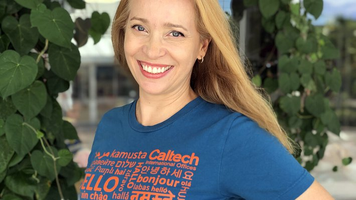 """Woman posing in a t-shirt that says """"hello"""" in many languages"""
