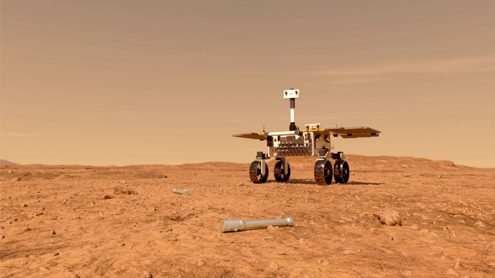 An artist's rendering of a small rover approaching silver metal tubes lying on the surface of Mars.