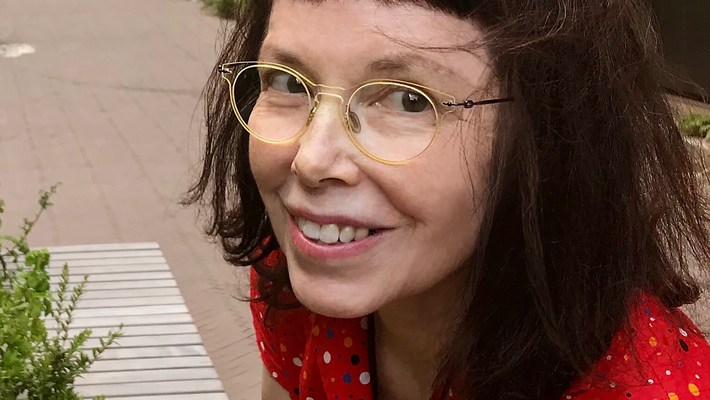 A portrait of artist Leslie Thornton. She wears a red dress and glasses.