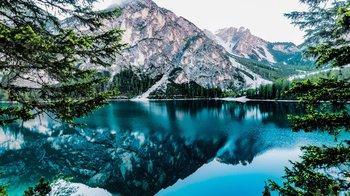 A lake reflects snowy mountains