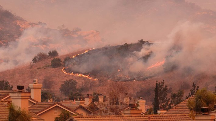 pink and orange image of a wildfire in the hills over a neighborhood